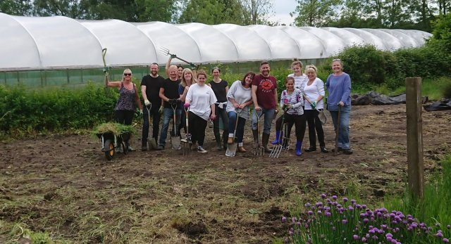 A group of volunteers standing on the land prepared to build a new polytunnel on