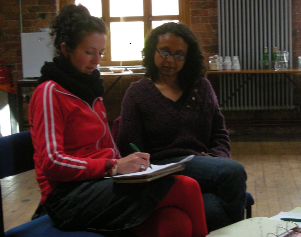 Two participants completing an action plan as part of the Strong Roots workshop